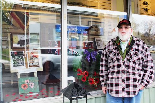 "Doug Lovegrove stands in front of the Remembrance display in the window of Nicole's Gifts in Verona. ""Nicky's been very supportive,"" he said. Photo/Craig Bakay"
