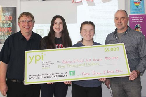 Annika Putnam and Mairina Jackson with teacher Randy McVety and principal James McDonald showint the $5,000 cheque that will be going to Addiction & Mental Health Services KFLA after Jackson and Putnam's winning presentation. Photo/Craig Bakay