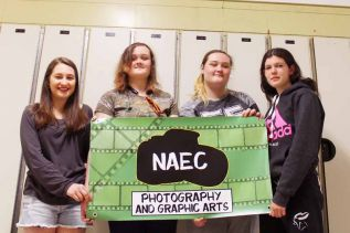 Natalie Reynolds, Brittany & Shannon Delyea and Terri-Lynn Rosenblath with the banner they designed for the Bon Echo Art Show. Photo by Summer Andrew.