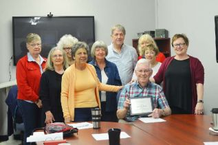 Alex McLeod (bottom right) receving a plaque tomark 24 years as a Food Bank volunteer