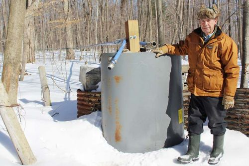 "Gary Gorr at one of his main lines in his sugar bush just south of Harrowsmith. ""Straight, tight and downhill,"" he said. Photo/Craig Bakay"
