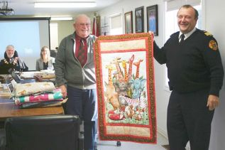 Coun. Gerry Martin and Fire Chief Eric Korhonen show off one of the quilts the Verona Trinity Quilters have donated to North Frontenac Emergency Services.