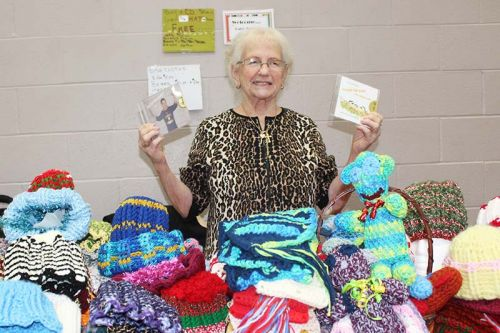 "Rev. Patsy Schmidt shows two of her CDs she was selling at the annual Christmas in the Village craft fair put on by the Harrowsmith Free Methodist Church Saturday. Schmidt is about to release her 10th CD of gospel music and has penned more than 150 songs. She was also selling her knitted hats, scarves and other items. She said knitting is good for her hands. ""The doctor told me to squeeze balls but that's a waste of time,"" she said. Photo/Craig Bakay"