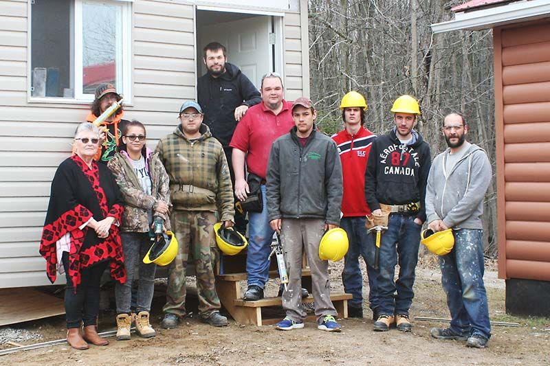 Work crew with Chief Davis in front of the new shed at the band office of the Shabot Obaadjiwan near Arden. Kevin Rioux (far right) Chief Davis (far left)