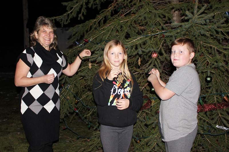 Melissa Elliott along with Kylie and Skylar Hickey, put some decorations on the tree donated by the Brown family out back of the Lions Hall in Verona last Friday night. Photo/Craig Bakay