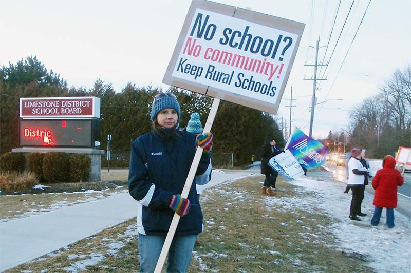 Robin Hutcheon, chair of the group called Rural Schools Matter, holds her sign outside the Limestone District School Board offices on Portsmouth Avenue in Kingston on November 8, 2017. She, along with about 30 others, are protesting the possible closure of all of the public schools in Stone Mills Township and the school in Selby.