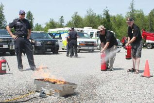 Coun. Gerry Martin and Mayor Ron Higgins take a turn at putting out a fire with extinguishers. The extinguishers demonstration was provided by Capt. Brian McCarthy, firefighter A.J. Watson and firefighter Jacob Green of the South Frontenac Fire Department.