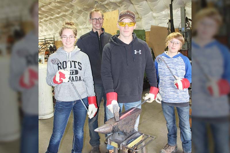 Class was in session last Saturday as master sculptor Stefan Duerst has being holding classes for kids. Here the Perry kids (Kaitlyn, Grant and Mason) are going through the various steps to create pokers and hooks. Photo/Craig Bakay