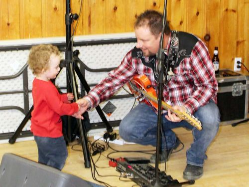 The next generation? Shawn McCullough gets congratulated by grandson Porter Badour during a gig last Sunday at the Sharbot Lake Legion with brother Dave. Photo/Craig Bakay