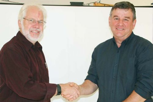 The changing of the guard. North Frontenac Public Works Manager Jim Phillips hands the reins to his replacement, Darwyn Sproule at last week's Council meeting. Phillips did say he'd be at the Dec. 15 meeting.