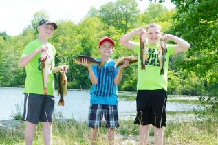Zack, Austin, and Josh, showing off their catch at the COFA fishing day last week.