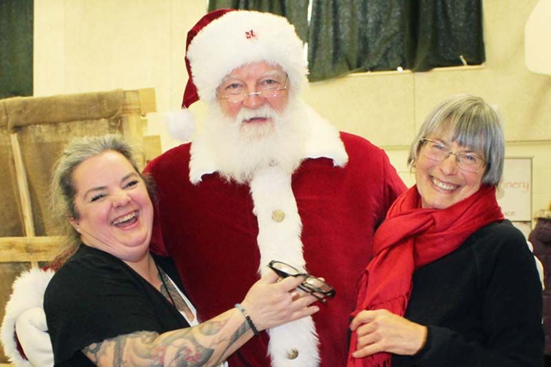 Organizers Alison Williams and Laura Simmons get a hug from Santa at the Holiday Market last Saturday in Prince Charles Public School. Photo/Craig Bakay