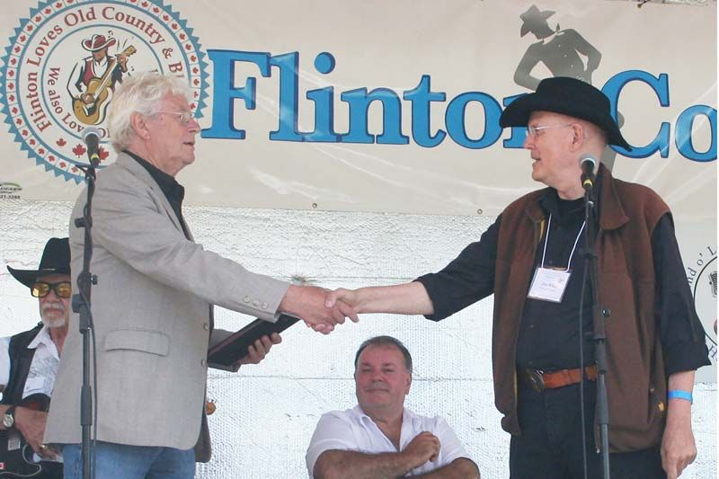 Neville Wells being inducted into the Land O'Lakes Traditional Music Hall of Fame by Don White Saturday at the Flinton Jamboree.