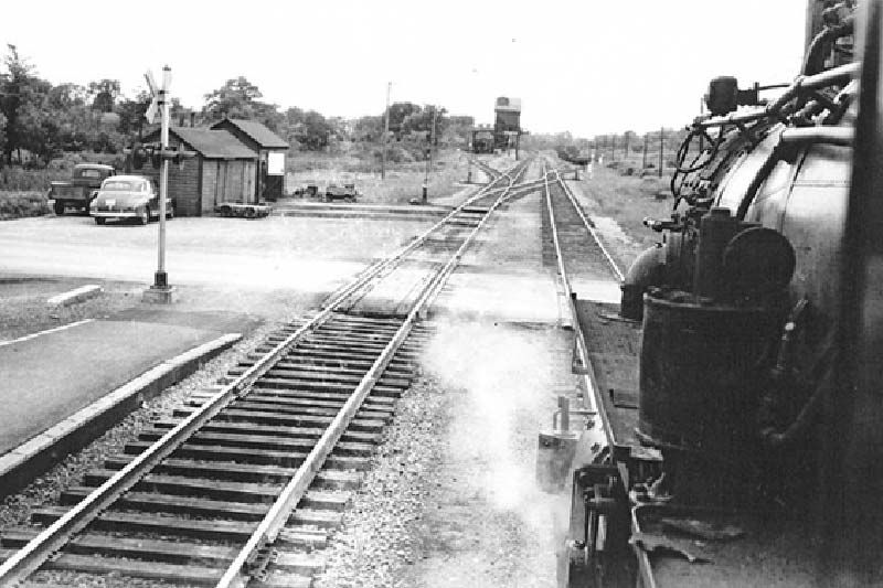 The photo shows the engineer's view of the grade crossing at Tichborne, where the steam engine has turned west onto the main CPR line to pick up coal at the coaling tower, visible in the background (The picture was taken by David Page in 1956.)