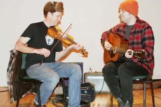 Teilhard Frost (fiddle) and Tom Power (guitar) warm up before the Maberly Quarterly square dance Saturday night in Maberly. Photo/Craig Bakay