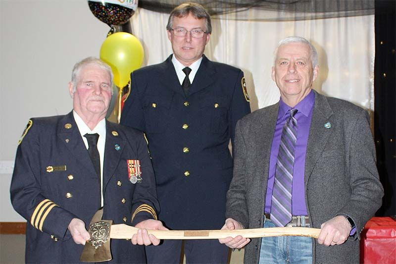 Dep. Chief Bill Babcock was presented with a commemorative fire axe by Dep. Chief Stan Ritchie and Mayor Ron Vandewal Saturday night in Harrowsmith. Photo/Craig Bakay