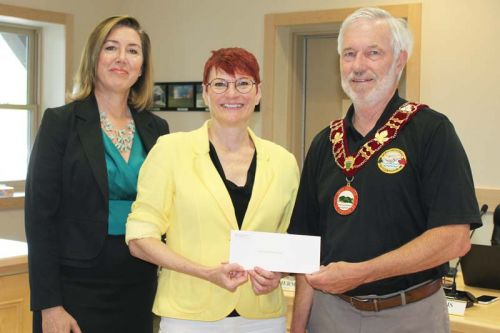 Debra Murphy (centre), Eastern Ontario regional manager for Frank Cowan Insurance and Megan Schooley from McDougall Insurance Brokers in Perth presented Mayor Ron Higgins with $5,000 from their Home Town Program to be used towards repairing Barrie Hall in Cloyne at the regular North Frontenac Council meeting last Friday in Cloyne. Photo/Craig Bakay