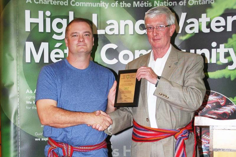 The Ontario Trillium Foundation's Jim Roulston presents High Land Waters Metis Community President Scott Lloyd with a plaque signifying a $75,000 seed grant awarded to the Community for its Mamawapowuk traditional knowledge project. Photo/Craig Bakay