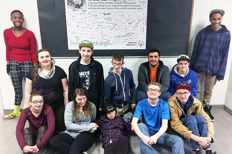 Students from the School to Community class at Granite Ridge Education Centre (GREC) in Sharbot Lake posing in front of a Spread the Word to End the Word poster that was signed by Granite Ridge students and staff.