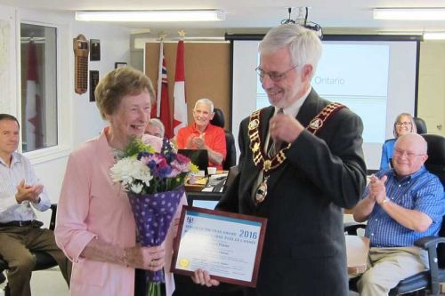 Eileen Flieler was presented with the Senior Of The Year Award by Mayor Ron Higgins to a full house of family and friends at the June 30 council meeting in Plevna.