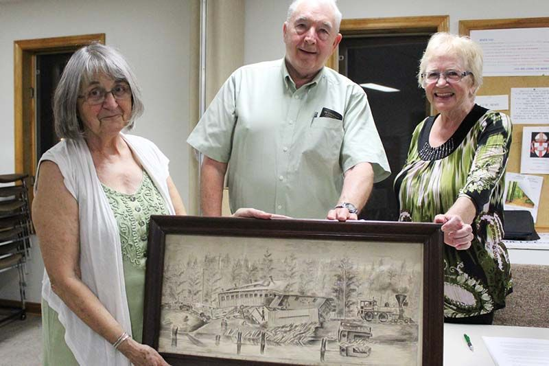 "Central Frontenac Railway Heritage Society directors Sally Angle, Wayne Moase and Barb Neill show the recently acquired depiction of a train wreck on the K & P April 22, 1879. The Society is currently ""scoping out"" a permanent home for the artifact. Photo/Craig Bakay"