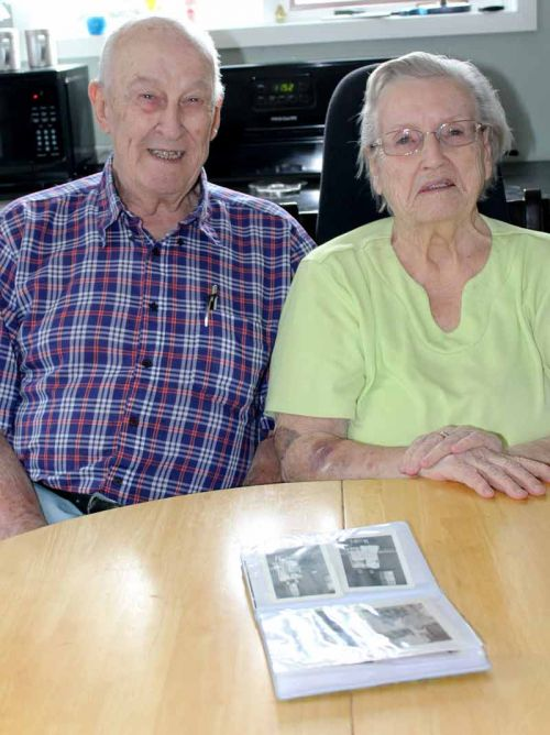 Eileen Whan and her husband Doug look over some old photos of Eileen and her pen pal Eileen. Photo/Craig Bakay