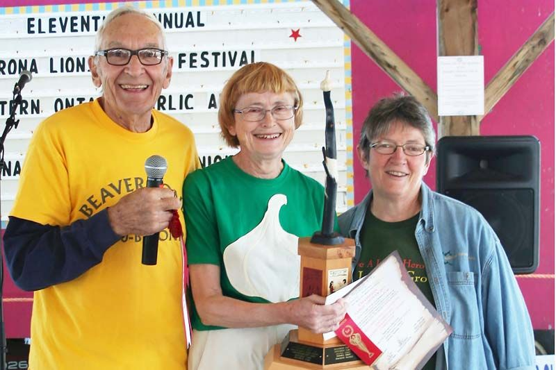 Garlic Guru Paul Pospisil and NFU president Dianne Dowling presented Dorothy Oogarah with the trophy as 2017 Champion at the 21st annual Eastern Ontario Garlic Awards Saturday in Verona. Photo/Craig Bakay