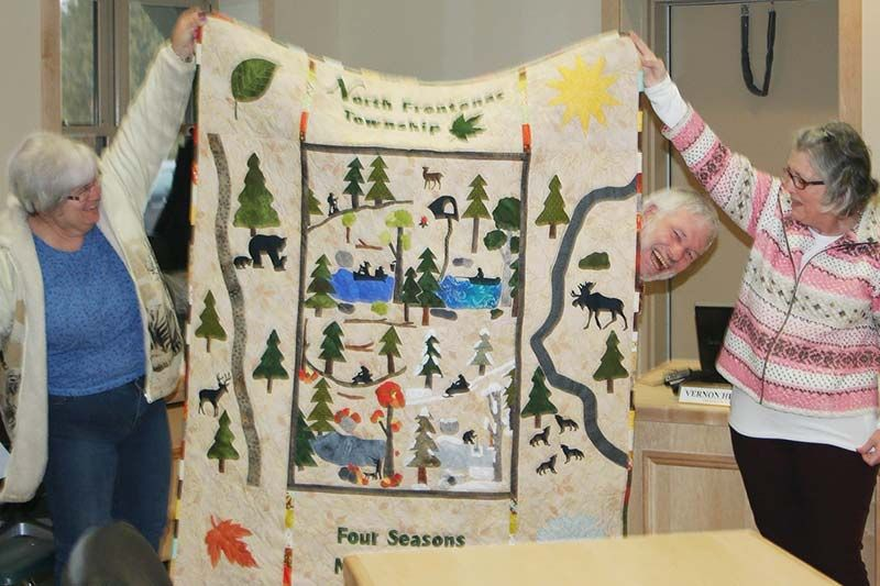 For the first meeting in the new Council Chambers, the Township received several decorative gifts including this quilt from Debbie Emery (right, with help from Betty Hunter and Mayor Ron Higgins it up for a picture) and a picture board from Coun. John Inglis.