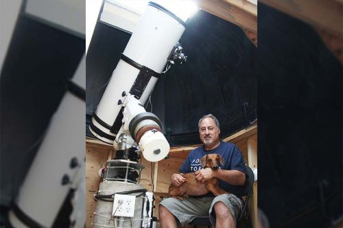 "Gary Colwell has some new toys including a MallinCam system that is specially designed to take pictures that aren't fuzzy. He's pictured here at his home observatory with his new 12"" telescope along with Bear, the cosmic dachshund. Photo/Craig Bakay"